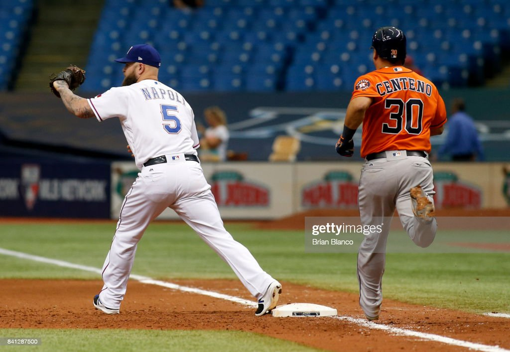 First baseman Mike Napoli #5 of the Texas Rangers hauls in the throw from shortstop Elvis Andrus to complete the double play with the out at first base on Juan Centeno #30 of the Houston Astros to end the seventh inning of a game on August 31, 2017 at Tropicana Field in St. Petersburg, Florida.