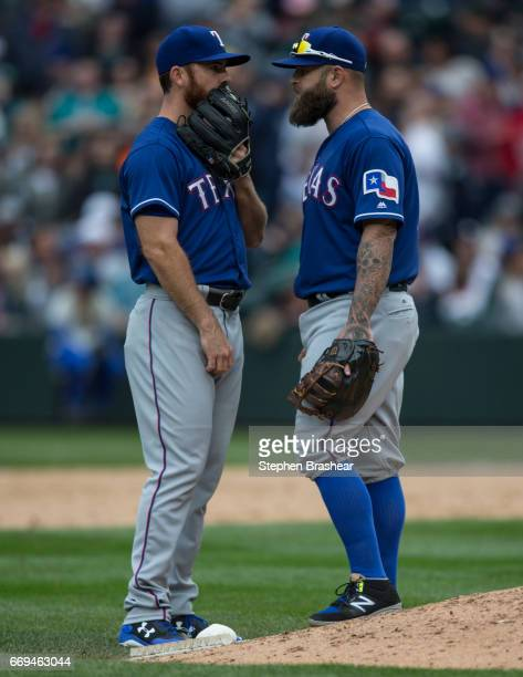 First baseman Mike Napoli right of the Texas Rangers meets at the mound with relief pitcher Sam Dyson during a game Texas Rangers at Safeco Field on...