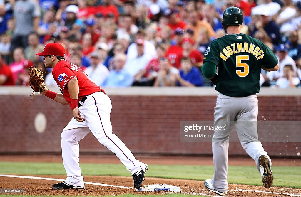 First baseman Mitch Moreland #18 of the Texas Rangers makes the out against Kevin Kouzmanoff #5 of the Oakland Athletics on July 29, 2010 at Rangers Ballpark in Arlington, Texas.