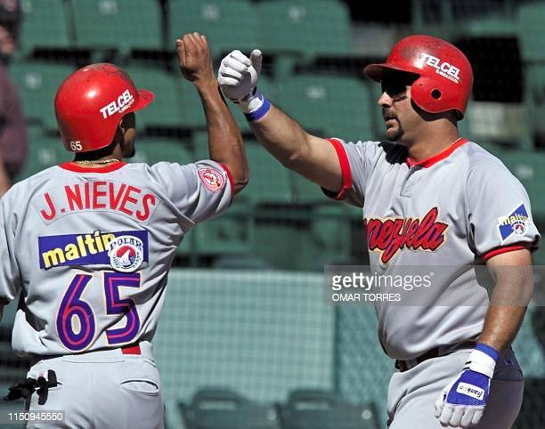First baseman of Venezuela's los Cardenales de Lara Luis Raven congratulates his teammate Joes Nieves after hitting a homerun in the Caribbean Series...