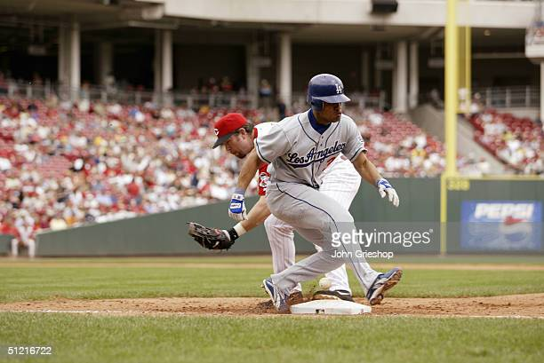 First baseman Sean Casey of the Cincinnati Reds fails to hold onto the ball as infielder Cesar Izturis of the Los Angeles Dodgers steps on base...