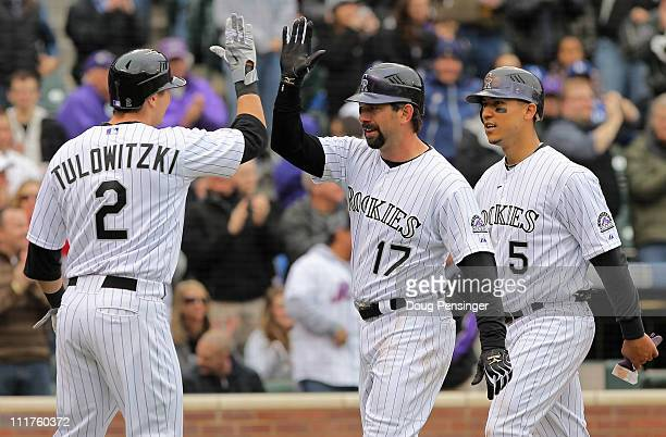 First baseman Todd Helton of the Colorado Rockies is welcomed home by Troy Tulowitzki of the Rockies and Carlos Gonzalez of the Rockies after they...