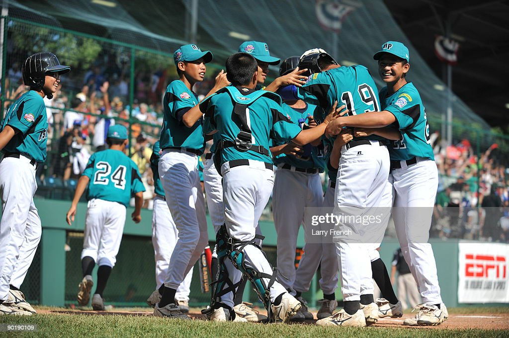 First baseman Wen Hua Sung #19 of Asia Pacific (Taoyuan, Taiwan) is mobbed by teammates after a home run against California (Chula Vista) in the little league world series final at Lamade Stadium on August 30, 2009 in Williamsport, Pennsylvania.