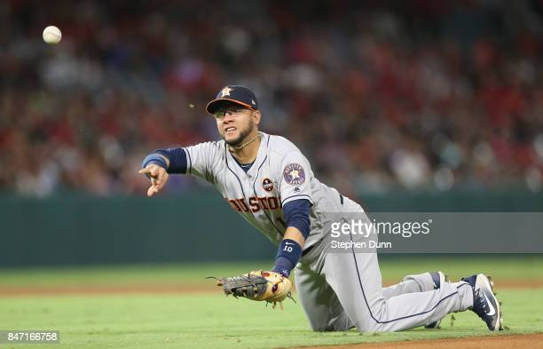 First baseman Yuli Gurriel of the Houston Astros flips the ball to pitcher Brad Peacock covering first base to get Martin Maldondo of the Los Angeles...