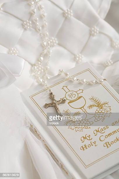 First communion book, rosary beads with silver cross, white religious dress