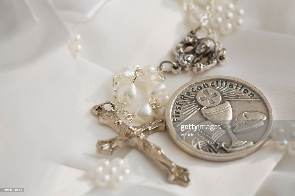 First communion book, rosary beads with silver cross, white religious dress : Stock Photo