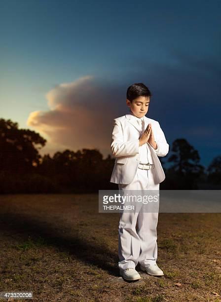 First communion boy praying