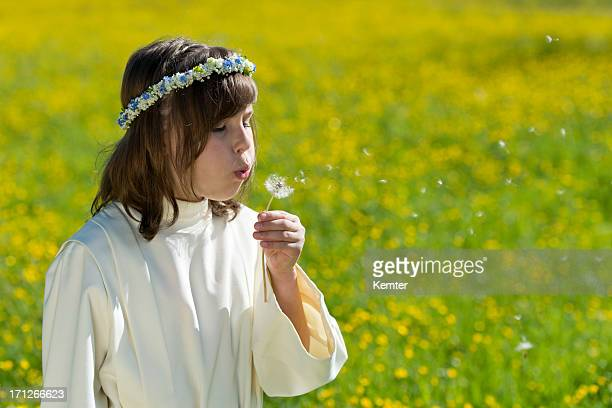first communion girl standing on a blooming meadow