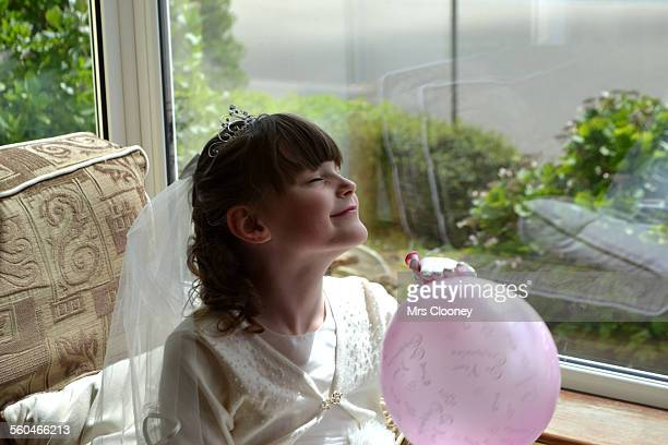 First Communion girl with pink balloon