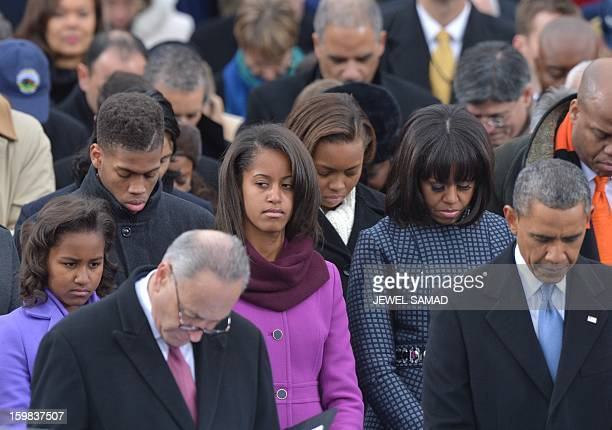 First daughters Sasha and Malia First Lady Michelle Obama President Barack Obama and Senator Charles Schumer listen to the National Anthem during the...