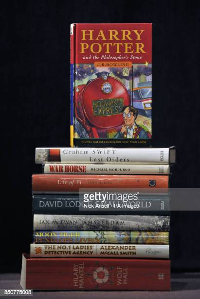 A first editon Harry Potter book annotated by author JK Rowling stands on a stack of other first editions on show as part of Sotheby's English PEN...