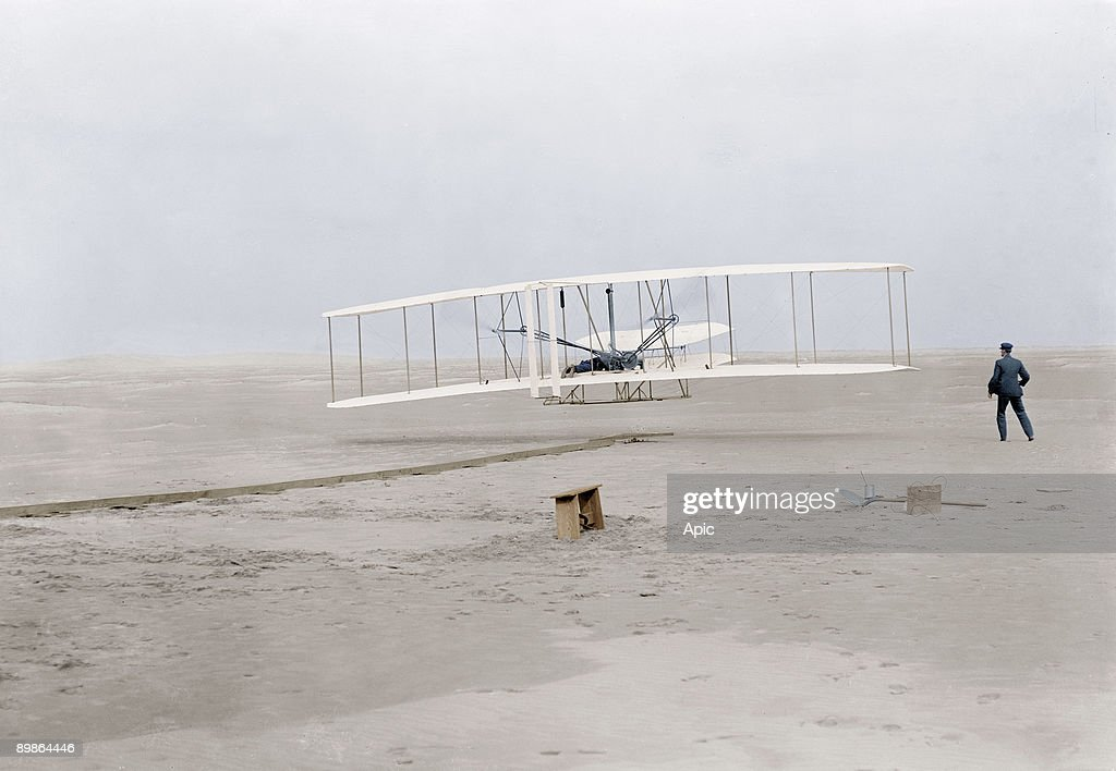 first flight of Orville Wright (1871-1948) at Kill Devil Hills, Kitty Hawk, North Carolina december 17, 1903 (120 feet in 12 seconds), his brother Wilbur Wright stand on the right : News Photo