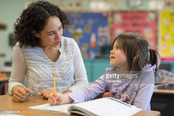 first grade girl talking with her teacher in the classroom - english language stock pictures, royalty-free photos & images