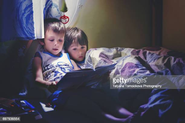 First grade school boy, reading a book in bed to his younger brother, night time