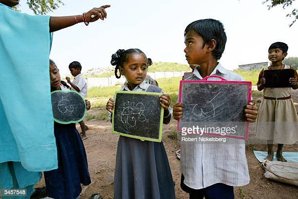 First grade students hold up their chalk boards in a rural school's language class as a teacher corrects their script and pronunciation of a Telegu...
