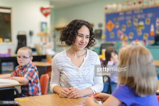 a first grade teacher talking with one of her students in the classroom - english language stock pictures, royalty-free photos & images