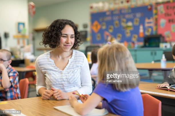 a first grade teacher talking with one of her students in the classroom - individuality stock pictures, royalty-free photos & images