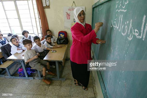 A first grade teacher writes in Arabic the words 'New Iraq' on the board on the first day of the new school year 04 October 2003 at the refurbished...