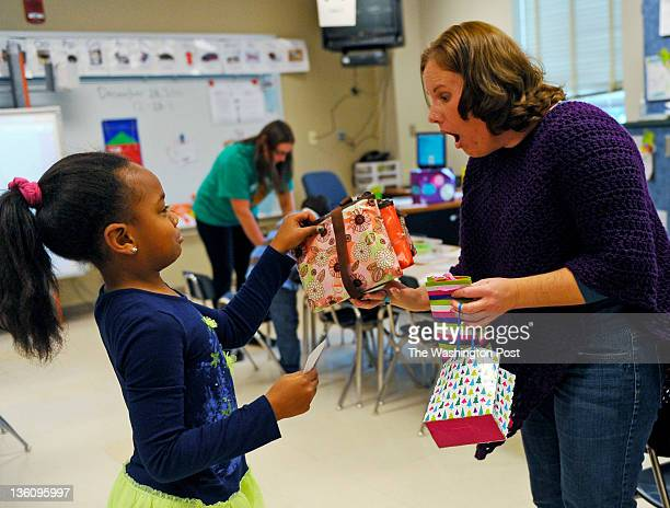 First grader Janae Harris presents her teacher Kelly Grinham with gifts including an ornament makeup bags and a mirror at Spark Matsunaga Elementary...