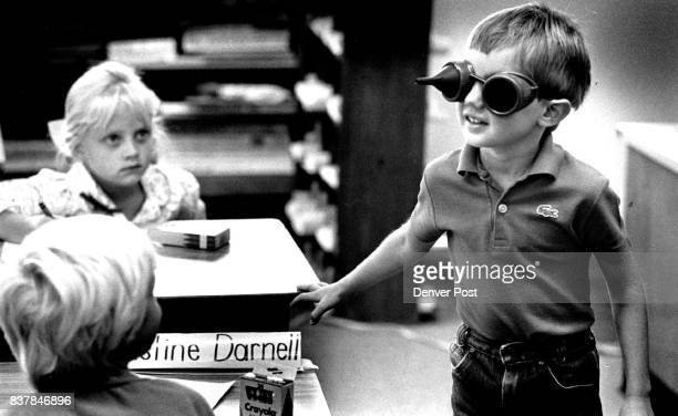 First grader Jason Hughes tries on goggles that simulate the vision of his first grade teacher Marge West who suffers from retinitis and will...