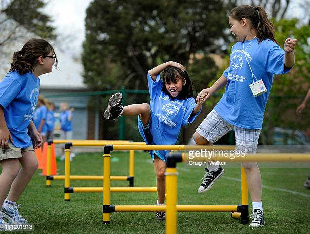 First grader Sueyen Laima of Asbury Elementary School gets a hand through the obstacle course from Eliza Kornfeld right and Ella Newcomb during...