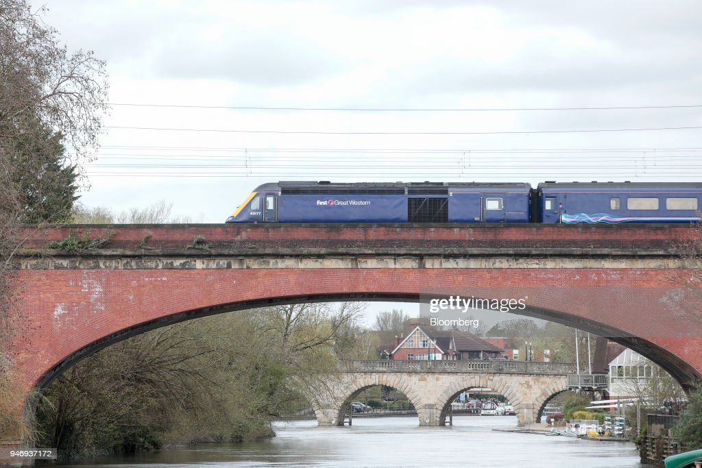A First Great Western train, operated by FirstGroup Plc, crosses the River Thames on the Maidenhead Railway Bridge near Maidenhead, U.K., on Monday, April 16, 2018. British train and bus operator FirstGroup Plc said it rejected an 'opportunistic' takeover proposal that private-equity firm Apollo Management made as the company struggles with under-performing rail routes in the U.K. and competition from discount airlines in the U.S. Photographer: Jason Alden/Bloomberg via Getty Images