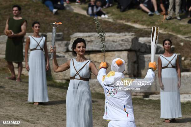 First Greek torchbearer for Pyeongchang 2018 crosscountry skier Apostolos Angelis receives the Olympic flame from actress Katerina Lechou acting the...