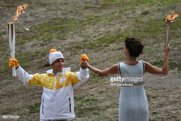 TOPSHOT First Greek torchbearer for Pyeongchang 2018 crosscountry skier Apostolos Angelis hands actress Katerina Lechou a Greek olive tree branch as...