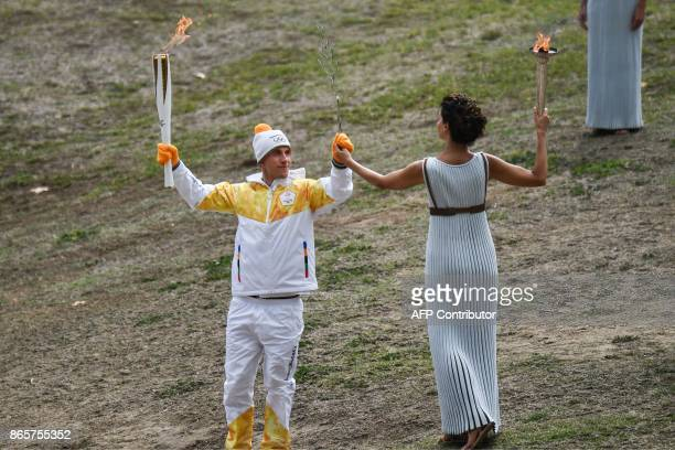 First Greek torchbearer for Pyeongchang 2018 crosscountry skier Apostolos Angelis hands actress Katerina Lechou a Greek olive tree branch as a symbol...