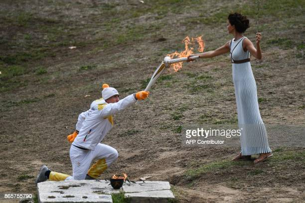 TOPSHOT First Greek torchbearer for Pyeongchang 2018 crosscountry skier Apostolos Angelis lights the OLympic torch to take the first relay from the...
