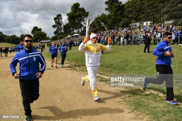 First Greek torchbearer for Pyeongchang 2018 crosscountry skier Apostolos Angelis holds the Olympic flame and a Greek olive tree branch as a symbol...