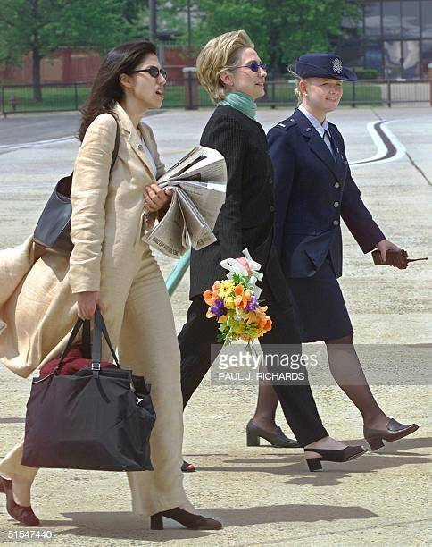 First Lady and New York Senate candidate Hillary Clinton carries flowers and is led by an unidentified Andrews Air Force Base Protocol Officer while...
