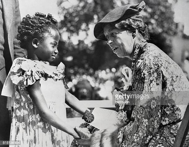 First Lady at Detroit's Slum Clearance Mrs Anna EleanorRoosevelt wife of the Chief Executive talks to fiveyearold Geraldine Walker at the ceremonies...