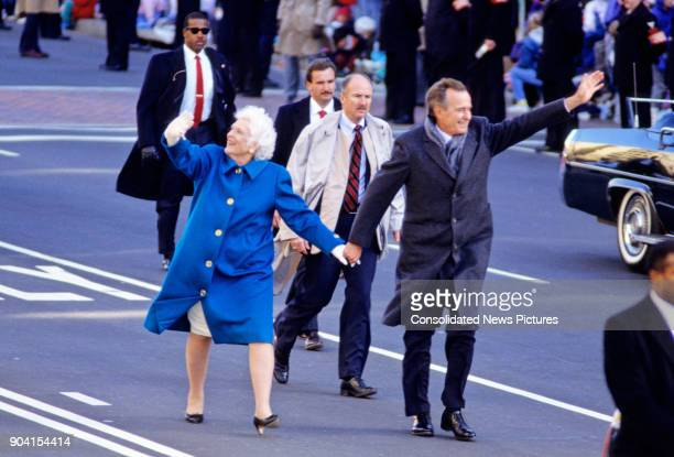 First Lady Barbara Bush and US President George HW Bush hold hands and wave as they lead the Inaugural Parade along Pennsylvania Avenue, Washington...