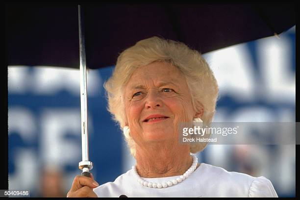 First Lady Barbara Bush sheltering under umbrella listening to her incumbent husband George speak at campaign rally