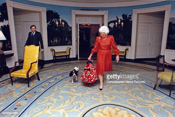 First Lady Barbara Bush walks her pet dog Millie through the White House's Diplomatic Reception Room Washington DC March 24 1989