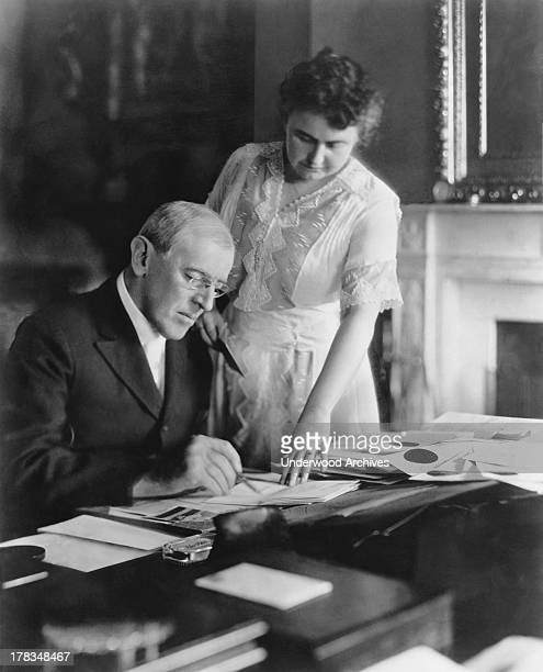 First Lady Edith Wilson assists President Woodrow Wilson at his desk in the White House, Washington DC, June, 1920.