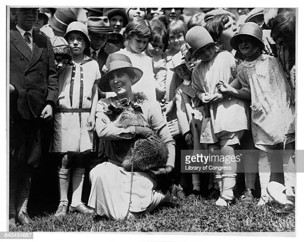 First Lady Grace Coolidge shows her pet raccoon to children gathered on the White House grounds for Easter egg rolling