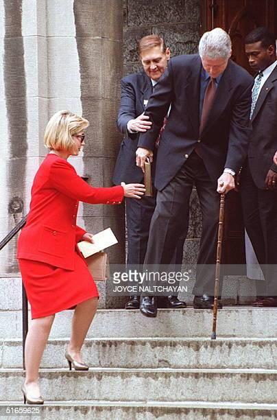 First Lady Hillary Clinton helps President Bill Clinton walk down the steps at the Foundry Methodist Church after Sunday services 25 May in...