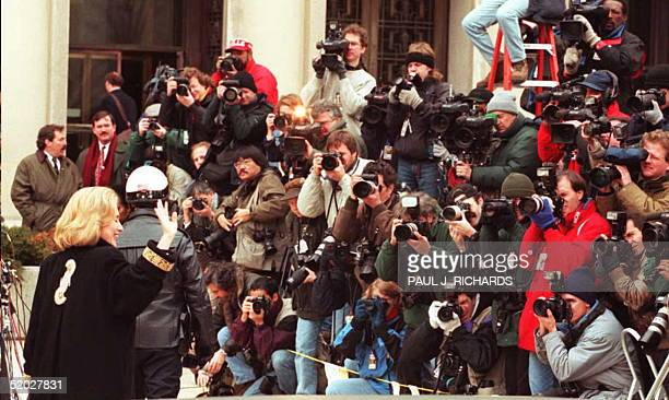 First Lady Hillary Clinton waves to the media 26 January 1996 as she arrives at Federal Court in Washington DC for an appearance before the Grand...