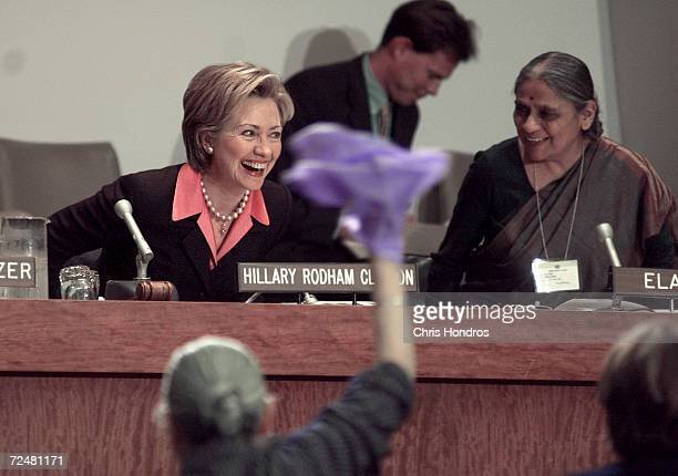 First Lady Hillary Rodham Clinton laughs next to Founder of the Self Employed Women's Assiociation of India Ela Bhatt after the audience sang We...