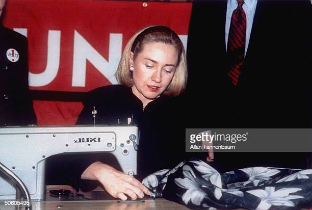 First Lady Hillary Rodham Clinton sewing a label into one of designer Nicole Miller's jackets to initiate the Union of Needletrades Industrial and...