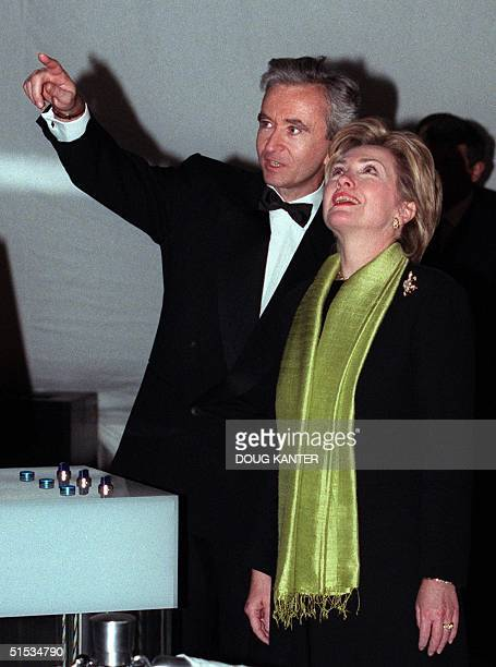 First Lady Hillary Rodham Clinton stands with Bernard Arnault as he points toward the new LVMH tower before the building's inauguration in New York...
