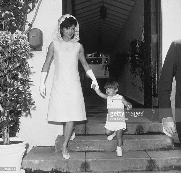 First lady Jacqueline Bouvier Kennedy and her son John F Kennedy Jr hold hands as they leave the home of Joseph P Kennedy after celebrating Easter...