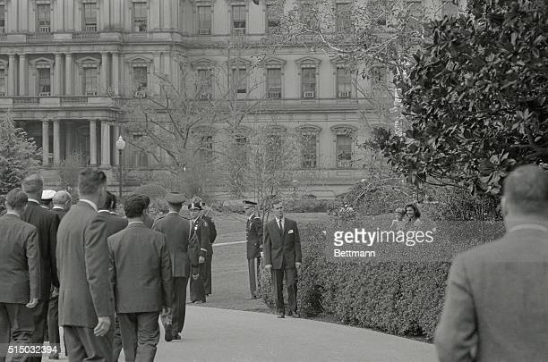 First Lady Jacqueline Kennedy and her son John watch from behind bushes in the Rose Garden as they watch the welcoming ceremonies for Algerian...