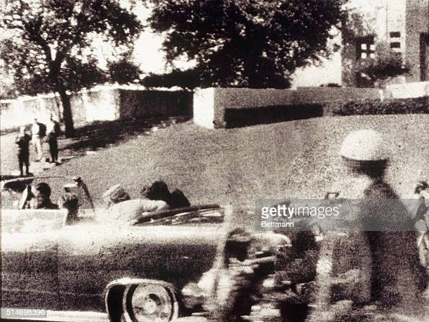 First Lady Jacqueline Kennedy leans over to assist her husband just after he is shot as the Presidential motorcade passes through Dealey Plaza on Elm...