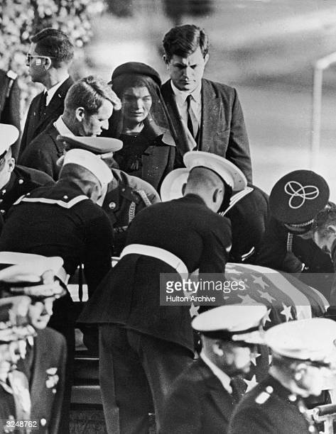 First Lady Jacqueline Kennedy stands between her brothersinlaw Robert and Edward Kennedy at the graveside of her husband assassinated President John...