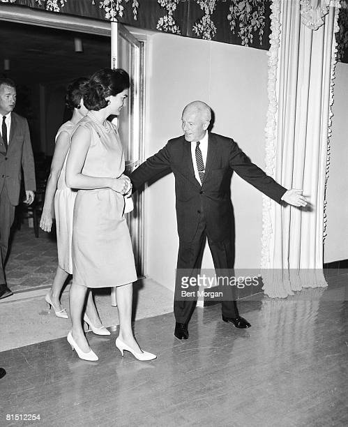 First Lady Jacqueline Kennedy the wife of US President John F Kennedy is escorted out of the auditorium of the Biltmore Hotel by Felix Standen Palm...