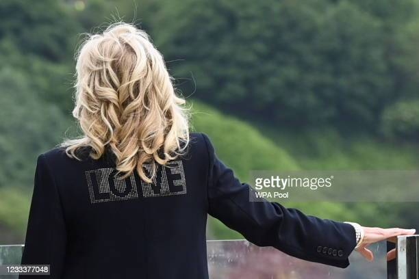 """First Lady Jill Biden, wearing a jacket with the phrase """"Love"""" on the back, stands outside the Carbis Bay Hotel on June 10, 2021 in St Ives, England...."""