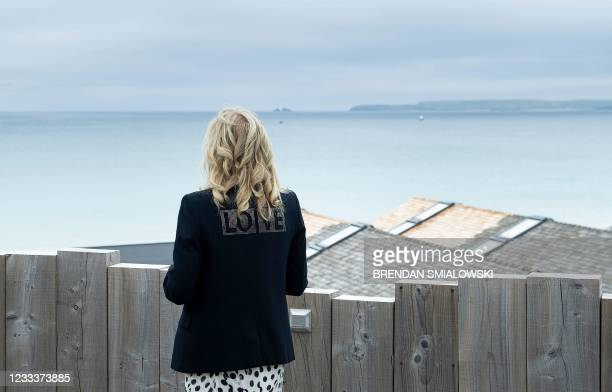 First Lady Jill Biden, wearing a jacket with the words 'love' on the back, poses for a photograph looking out over the sea, at Carbis Bay, in...